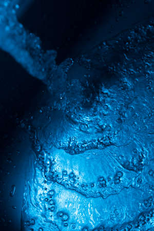 Blue water stream flowing over metallic surface photo