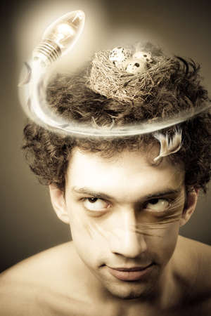 mystique: Man with nest on his head looking up flying light bulb. Creativity conceptual image Stock Photo