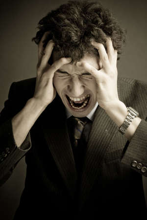 Young businessman screaming with hands on his head.Emotional business trouble concept. Stock Photo