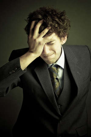Young sad businessman with hands on his head.Emotional business trouble concept. Stock Photo