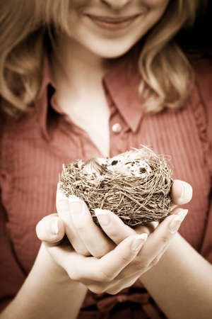 enviromental: Young woman holding a bird nest in her hands. Conceptual enviromental cheerful image.