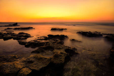 Wild nature seascape. Mighty big stones on a coastline and to horizon and red-orange sky photo