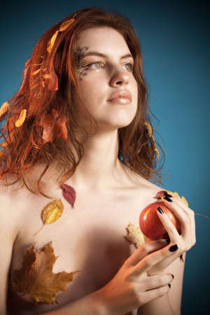 Young blond-brown seductive woman with autumn leaves in hair holding an apple. Natural beauty artistic portrait. photo