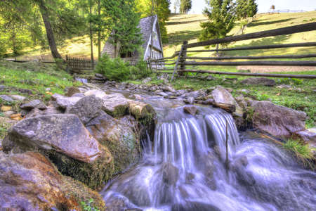 Countryside mountainous landscape with old house, wooden fence and water stream on foreground. Beautiful idyllic rural scene. photo