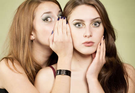 One girl whispering to other some news. Surprised face and palm near face in second girl Stock Photo