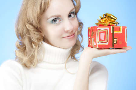 Attractive blond girl in warm clothing holding a red Christmas gift