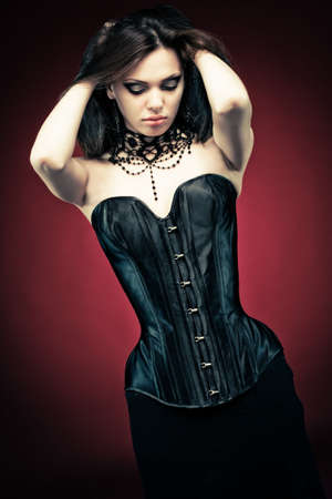 Modern style gothic woman in black leather corset on red vampire background. Hands on head, looking down.