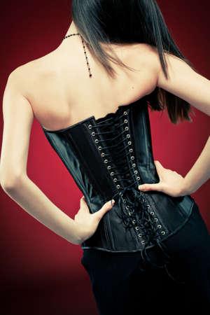 Modernen Stil gotischen Frau in schwarz Leder-Korsett auf red Vampire-Hintergrund. Hands on Taille, stehend zurück auf die Kamera.