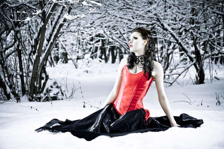 Well-dressed fashion model in red corset sitting alone in winter forest. Professional makeup and hair style. photo