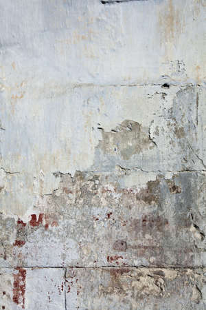 Weathered urban old wall with bloody stains and peeled stucco Фото со стока