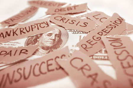 regression: Business concept image  Dollar bank-note laying with peaces of paper with inscriptions  Bankruptcy, crisis, regression, failure in business concept  Focus on franklin eyes  Red colored image  Stock Photo
