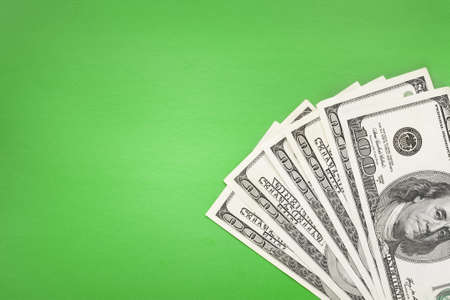 100  banknotes lying in corner on green simple background  photo