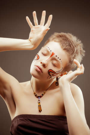ceremonial make up: Fashion artistic portrait of young woman with closed eyes  Maya style face painting, hands articulation, butch haircut  Focus on eyes