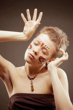 body paint: Moda artística retrato de una mujer joven con los ojos cerrados pintura maya estilo de la cara, la articulación de las manos, Enfoque butch corte de pelo en los ojos Foto de archivo