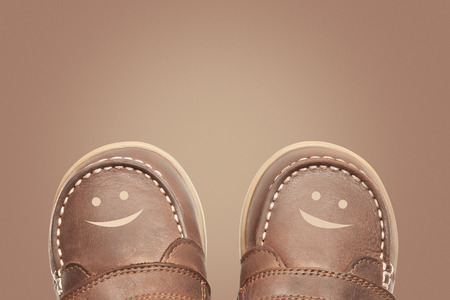 Brown smiling baby boots. Conceptual image with shoes characters. Happy shoping, child's joy concept