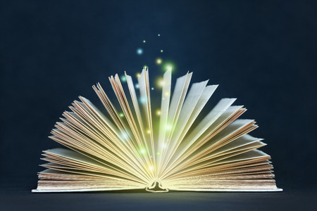 Open glowing magic book with flying lights Фото со стока