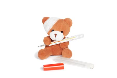 Teddy bear with bandage sitting and holding termometer. Illness, complication after injury, high temperature concept. Toy on white, isolated