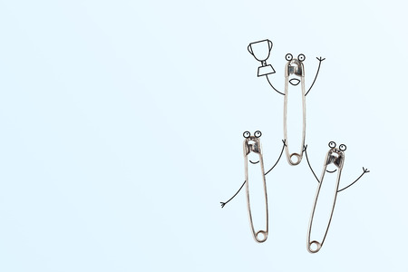 Three safety pins celebrating victory: two holding a winner with the cup in the hand. Funny cartoonish concept.