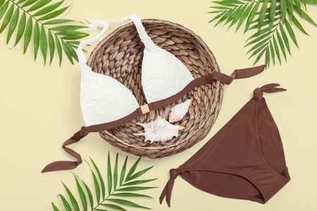 Swimwear set, wicker basket, seashells and palm leaves, top view. Summer style womens clothing set