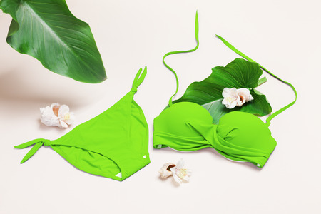 Green swimwear (bra and panties) set with sea shells, flowers, palm leaves. Summer travel fashion composition.