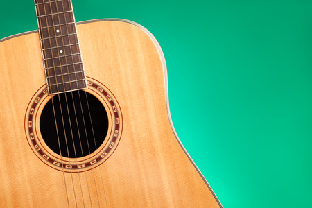 Part of acoustic guitar on green background with copy space
