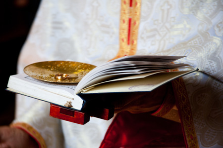 toog: priester in soutane en een bijbel op een bruiloft