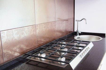 Kitchen - cooking area with gas stove and tile wall photo