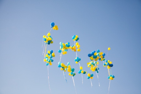 Bright colorful inflatable balloons up in air over blue sky background.