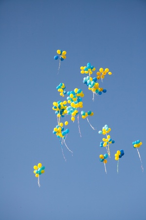 photo of object s: Bright colorful inflatable balloons up in air over blue sky background.