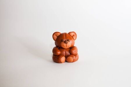 Plasticine chocolate happy bear with gift holiday boxes on a white background