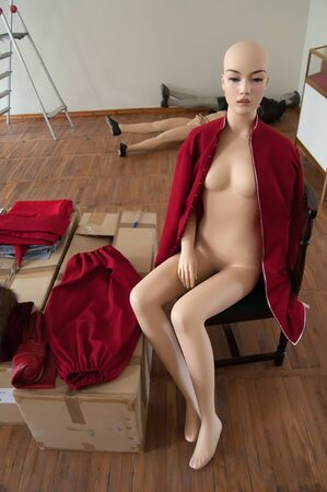 dummies: Mannequin during dressing, sitting on a chair against a background of other dummies.