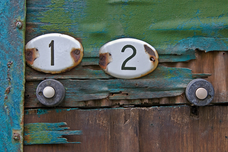 enameled: Enameled metal plates with the numbers of apartments on the old wooden door