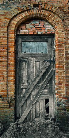 Old closed wooden door in an old house from a red brick Imagens