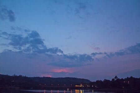 sangkhla buri: Twilight sky in the evening light on the water surface Stock Photo
