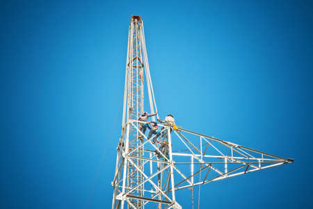 Workers are building high electricity post photo