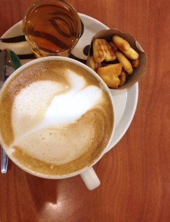 art: Cappuccino coffee and bread on the table Stock Photo