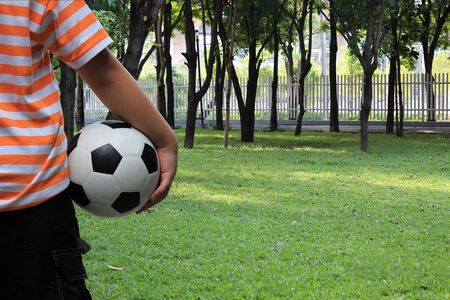 planing: A boy is holding soccer ball in a park and planing to play it.