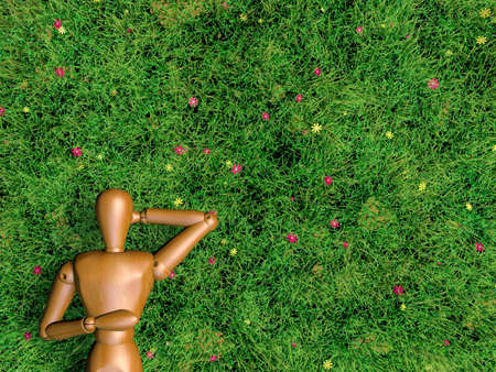 Wooden man is sleeping on grass lawn photo