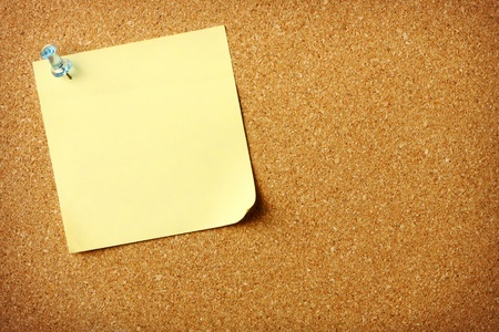 Blank sticky note pinned to corkboard background photo