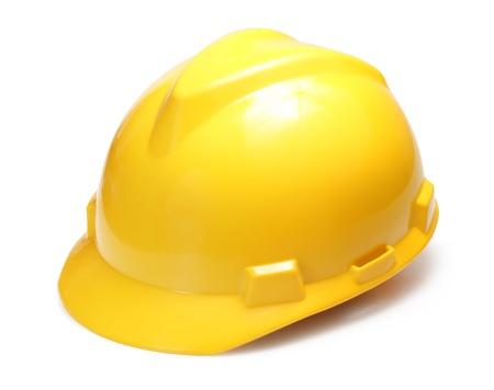 trabajando duro: Sombrero de construcci�n amarillo duro aislado en blanco