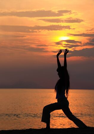 A woman exercisingstretching at sunset by the beach photo