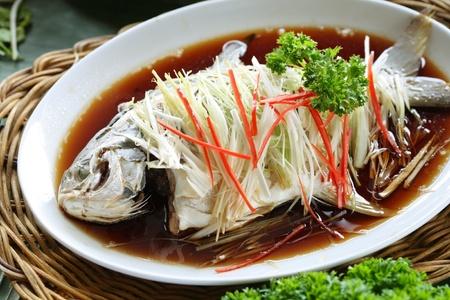 plato de pescado: Plato oriental pescado entero, cocido al vapor con salsa de soja y adornado con jengibre