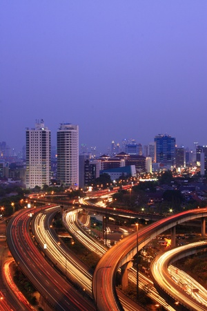 City skyline with multiple flyovers with busy traffic light trails Stock Photo