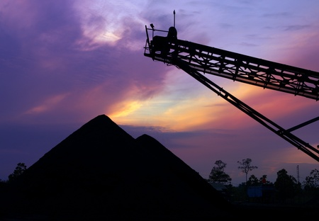 Mining landscape silhouette of coal stock at sunrise photo