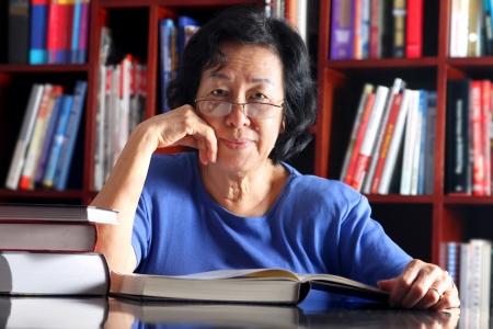 Señora mayor asiática leyendo un libro en la biblioteca Foto de archivo - 15203526