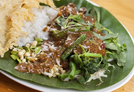 Nasi pecel is a Javanese rice dish served with mix vegetables and peanut sauce Stock Photo