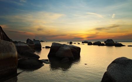 Dramatic sunrise in rocky beach