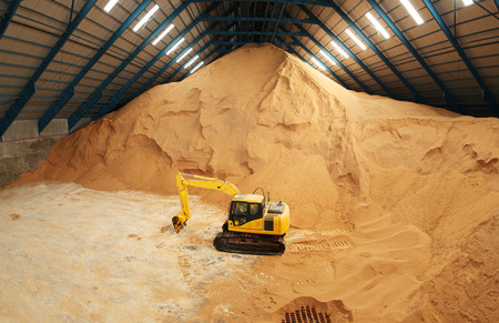 Excavator in a raw sugar factory storage building