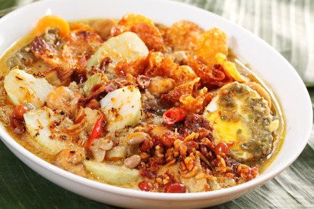 Lontong Sayur, an Indonesian specialty culinary dish consist of rice cake, bean curd, egg, peanut, and vegetable in spicy curry coconut milk broth Stock Photo