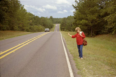 Woman standing by Highway trying to hitch a ride
